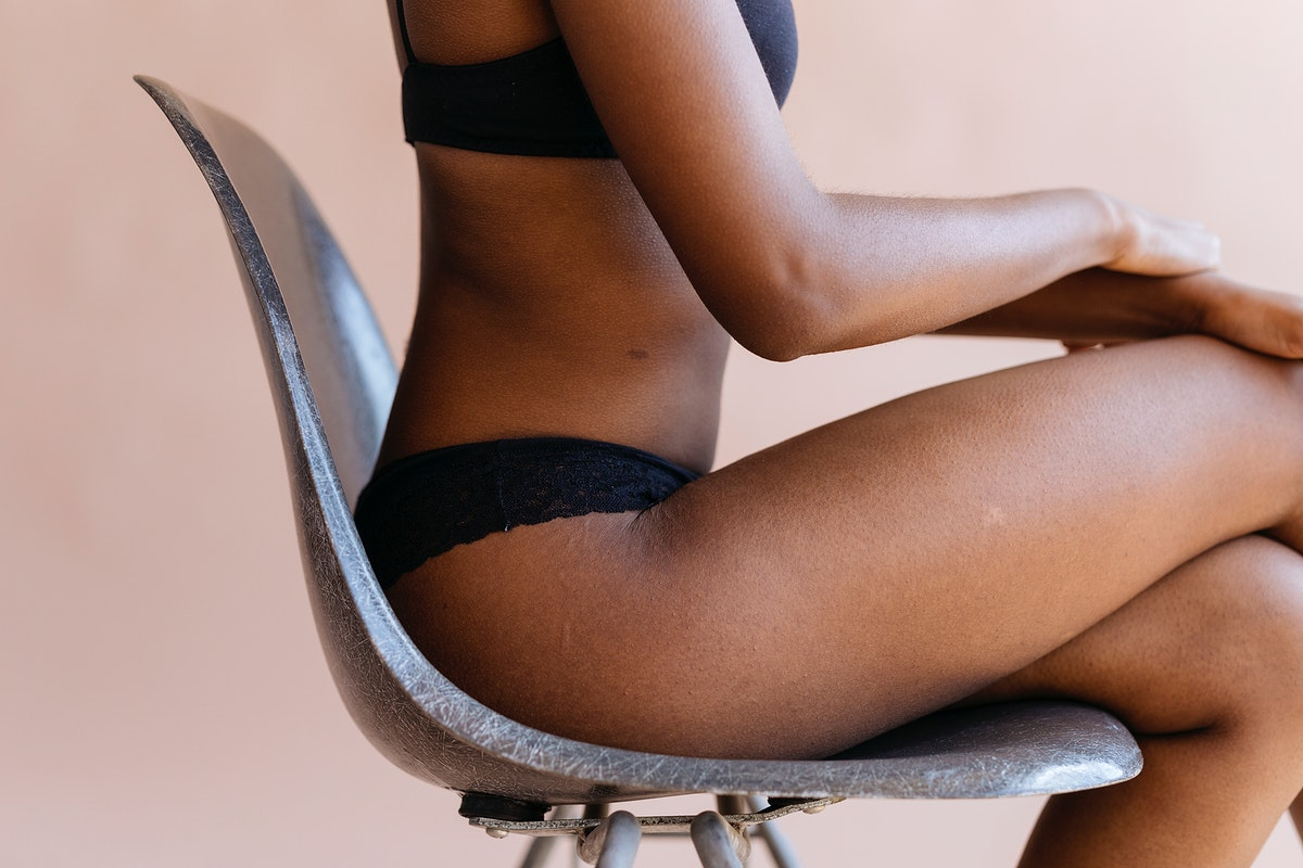 Woman in a black bra sitting on a chair