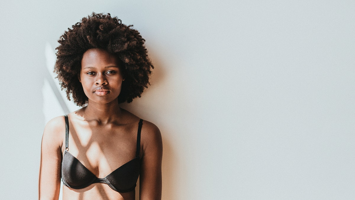 Black woman in a bra standing against a white wall