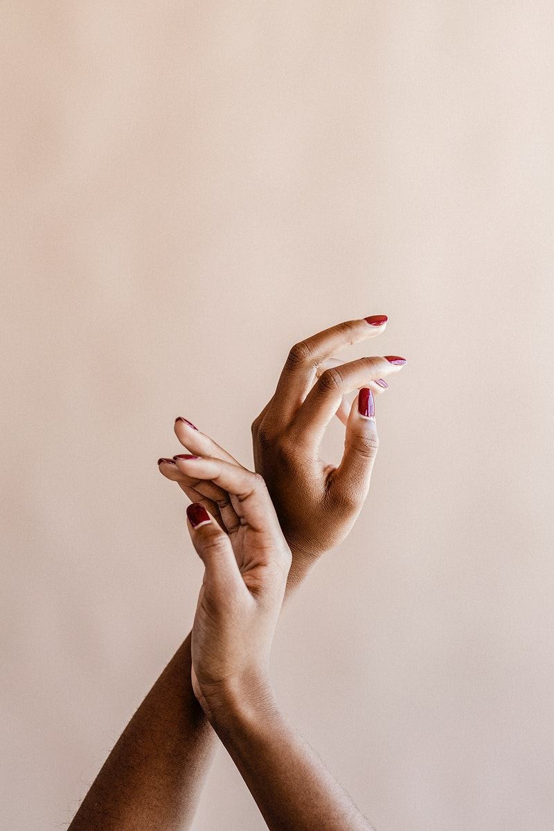 Two hands on a beige background