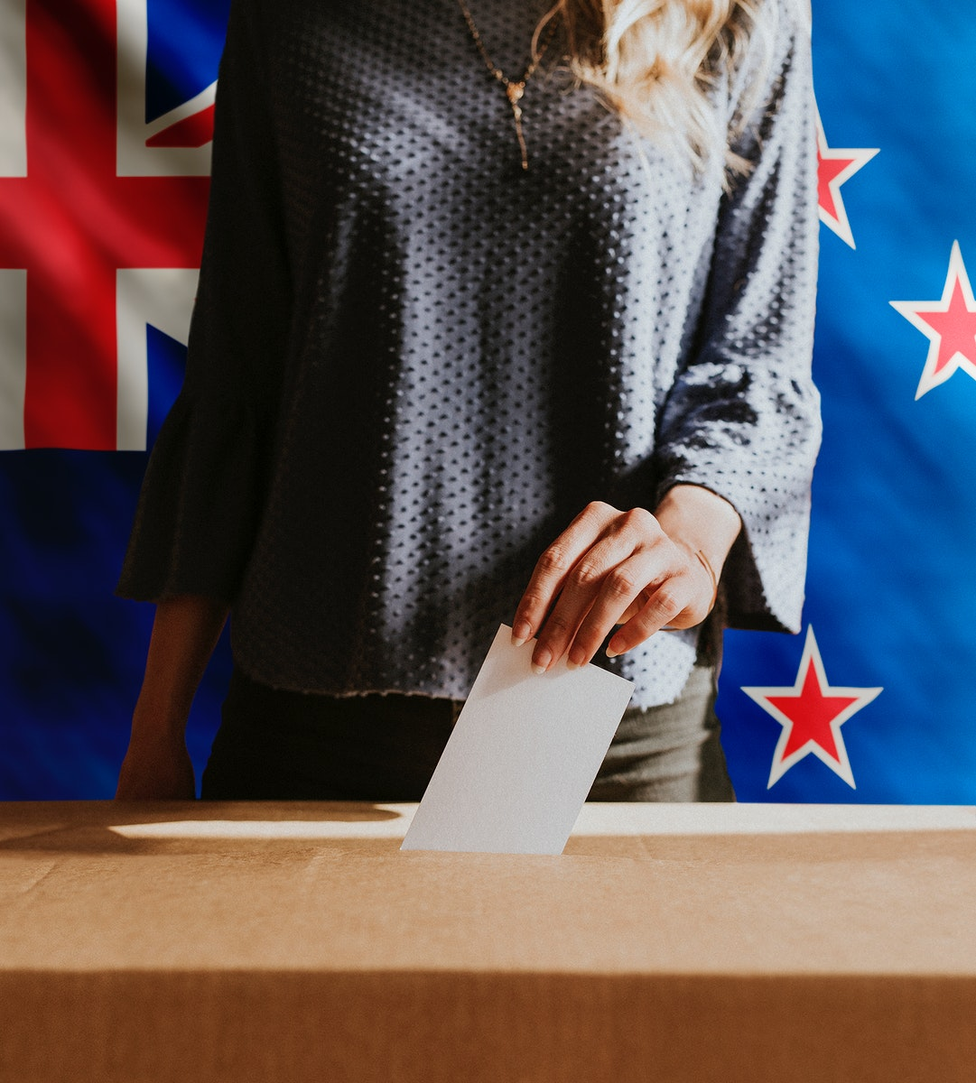 New Zealander woman putting a vote card into poll box