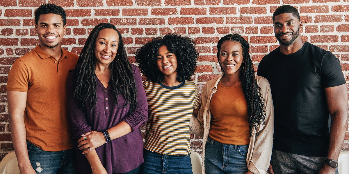 Cheerful black people standing in front of a red brick wall