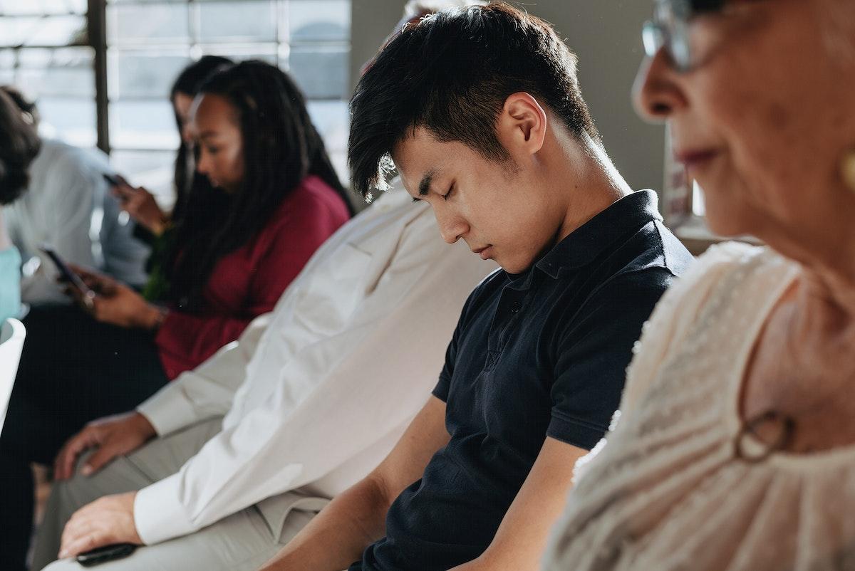 Tired young Asian man falling asleep in a seminar