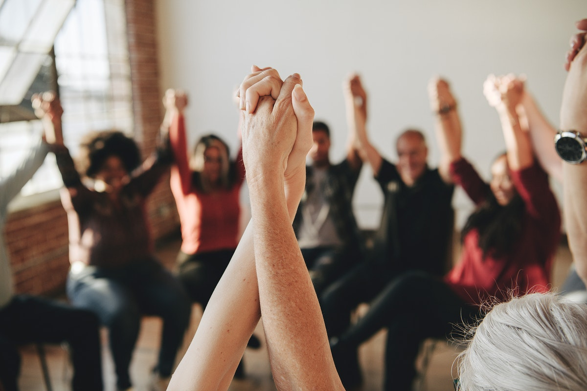 Group of diverse people holding hands up in the air