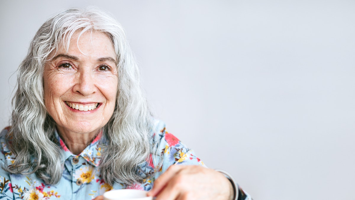 Cheerful grandmother sipping coffee in a cafe