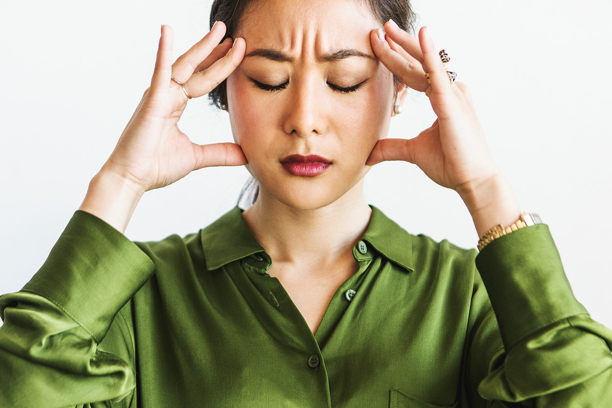 Stressed woman holding her forehead