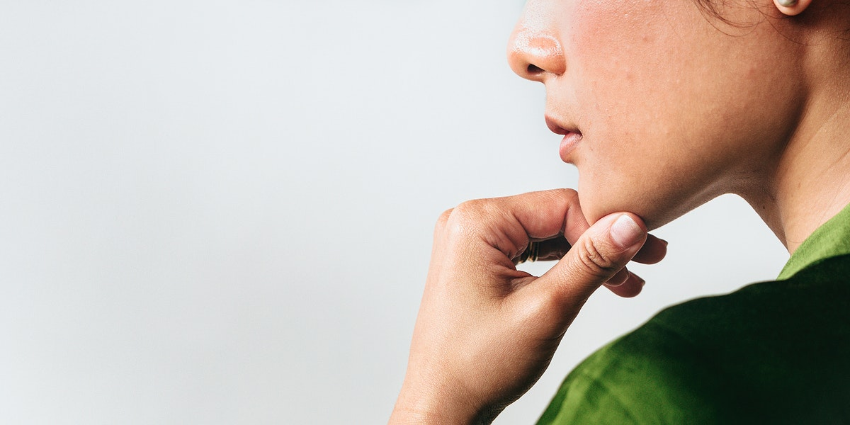 Woman holding her chin against a white wall