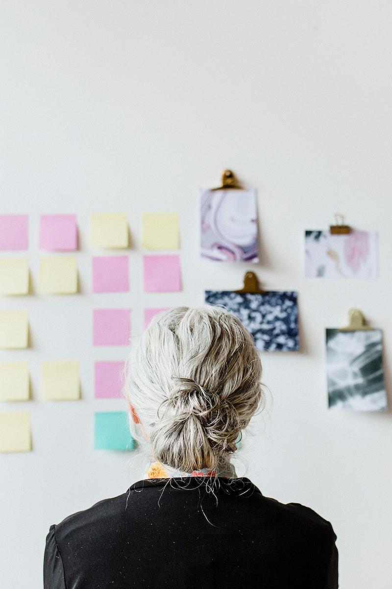 Senior businesswoman brainstorming ideas on a wall