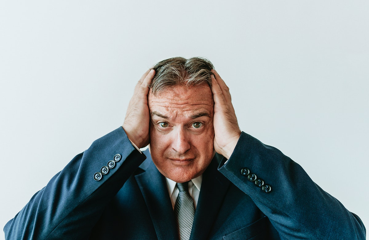 Stressed aged businessman touching his head