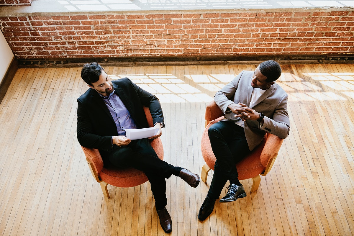 Businessmen talking and sitting on chairs