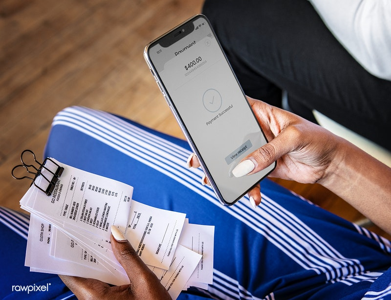 A woman doing banking and making payments on the smartphone she's holding in one hand, while also holding receipts in the other hand