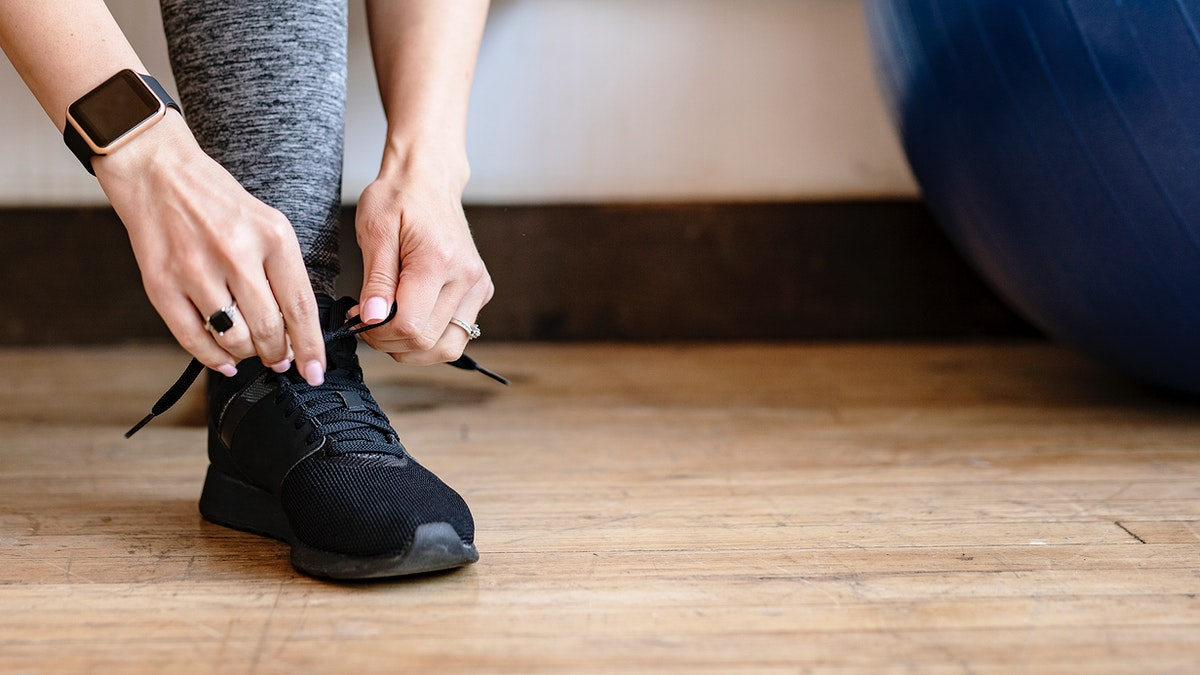 Active woman wearing a smartwatch tying her shoelaces