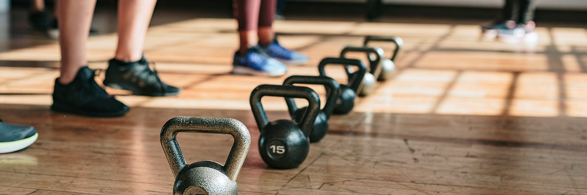 People standing by kettlebells in the gym