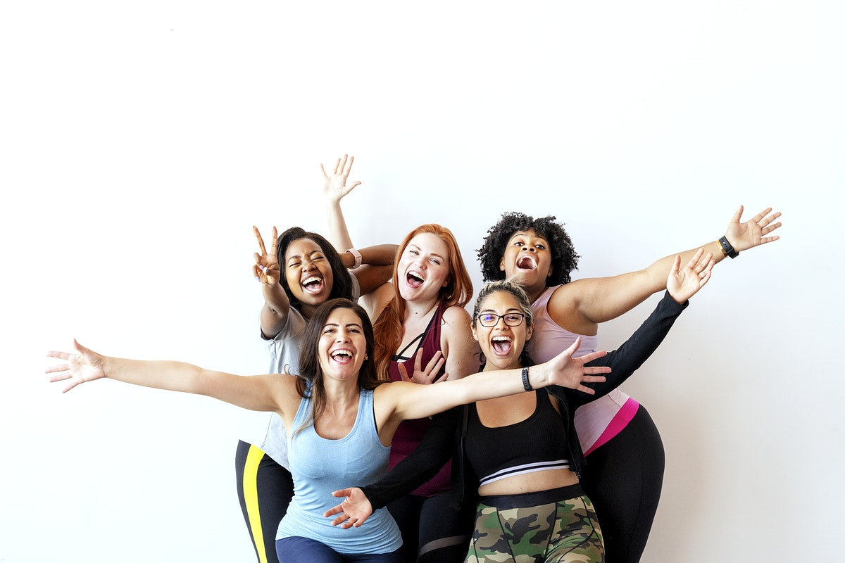 Group of happy sportive women with a white wall