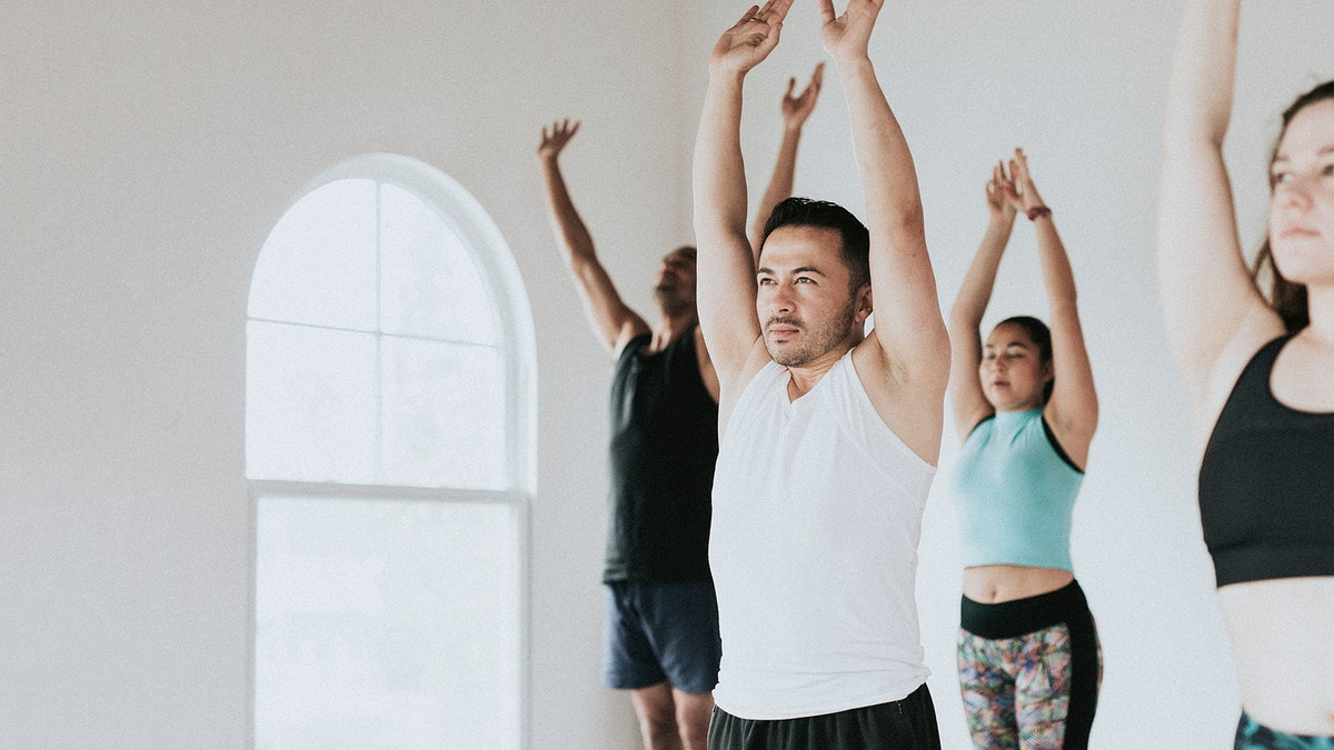 Group of people doing full body stretching in a class