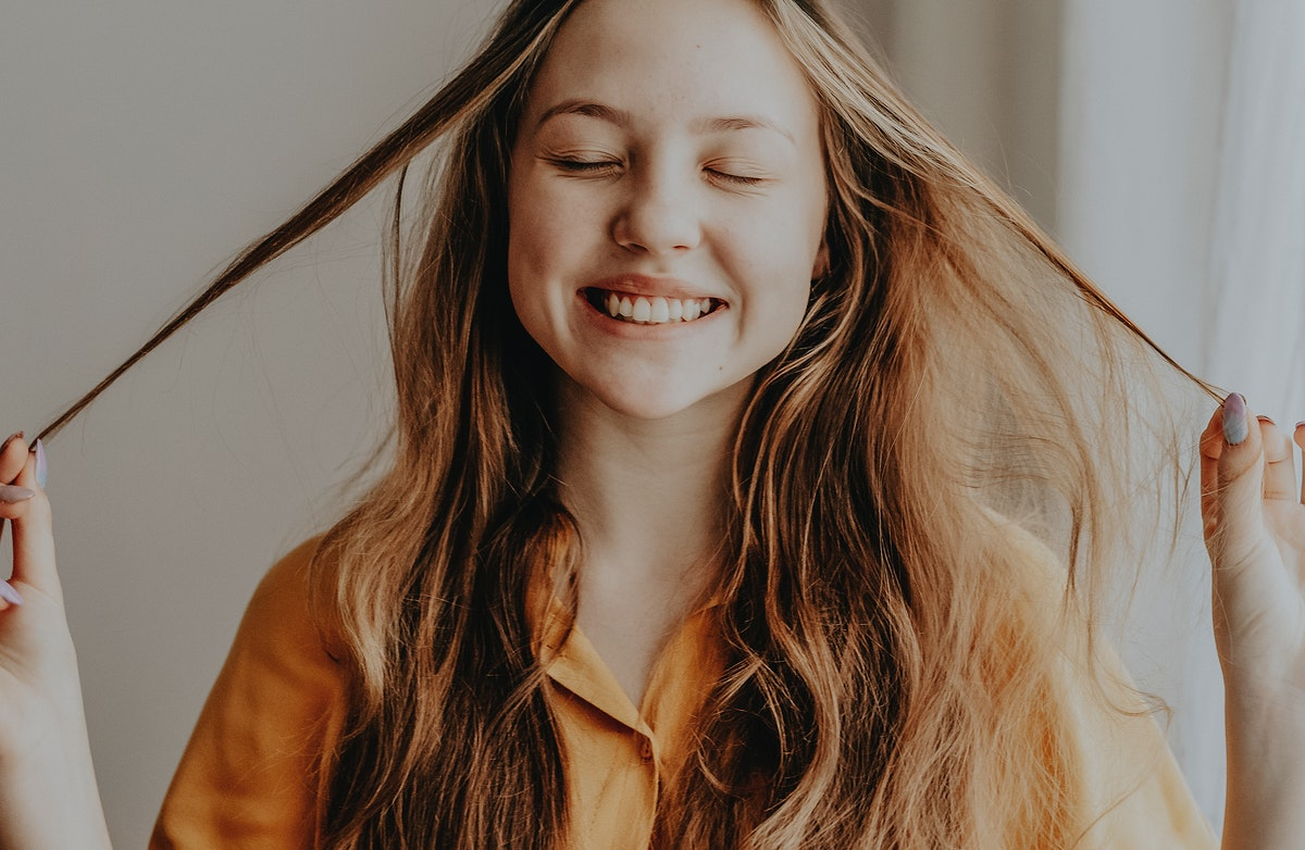 Cheerful blond girl playing with her hair