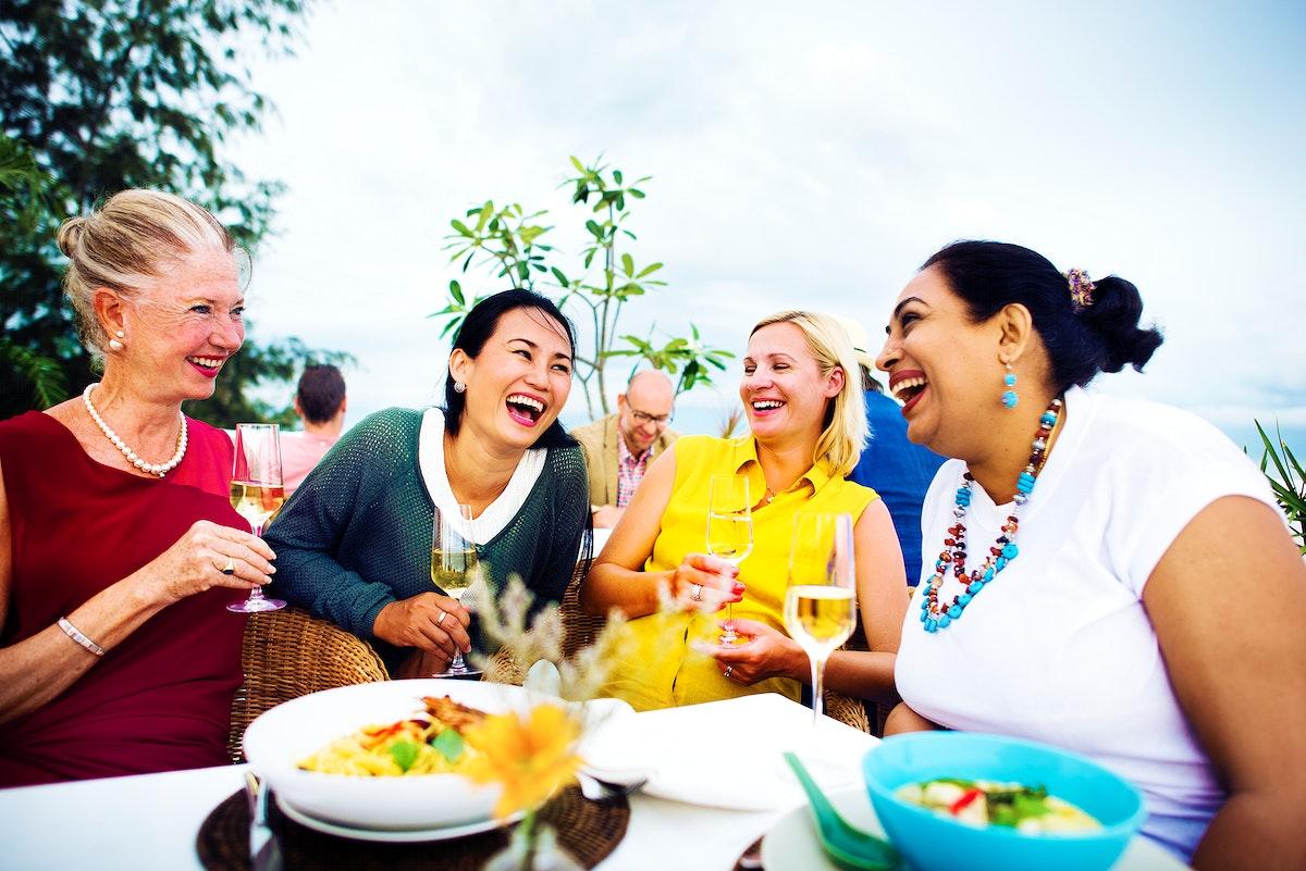 Female friends having dinner by the beach