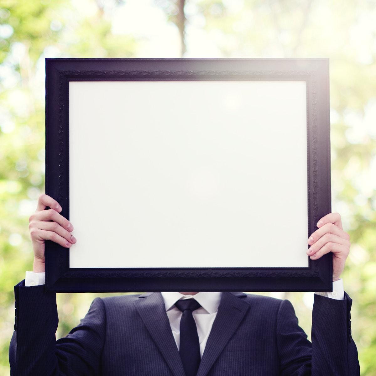 Businessman outdoors holding an empty placard
