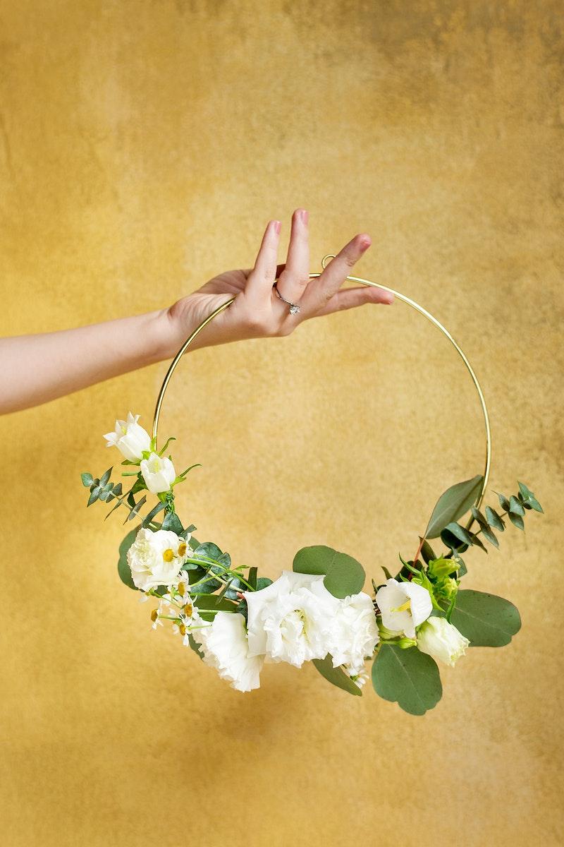 Girl holding a leaf decorated round golden frame