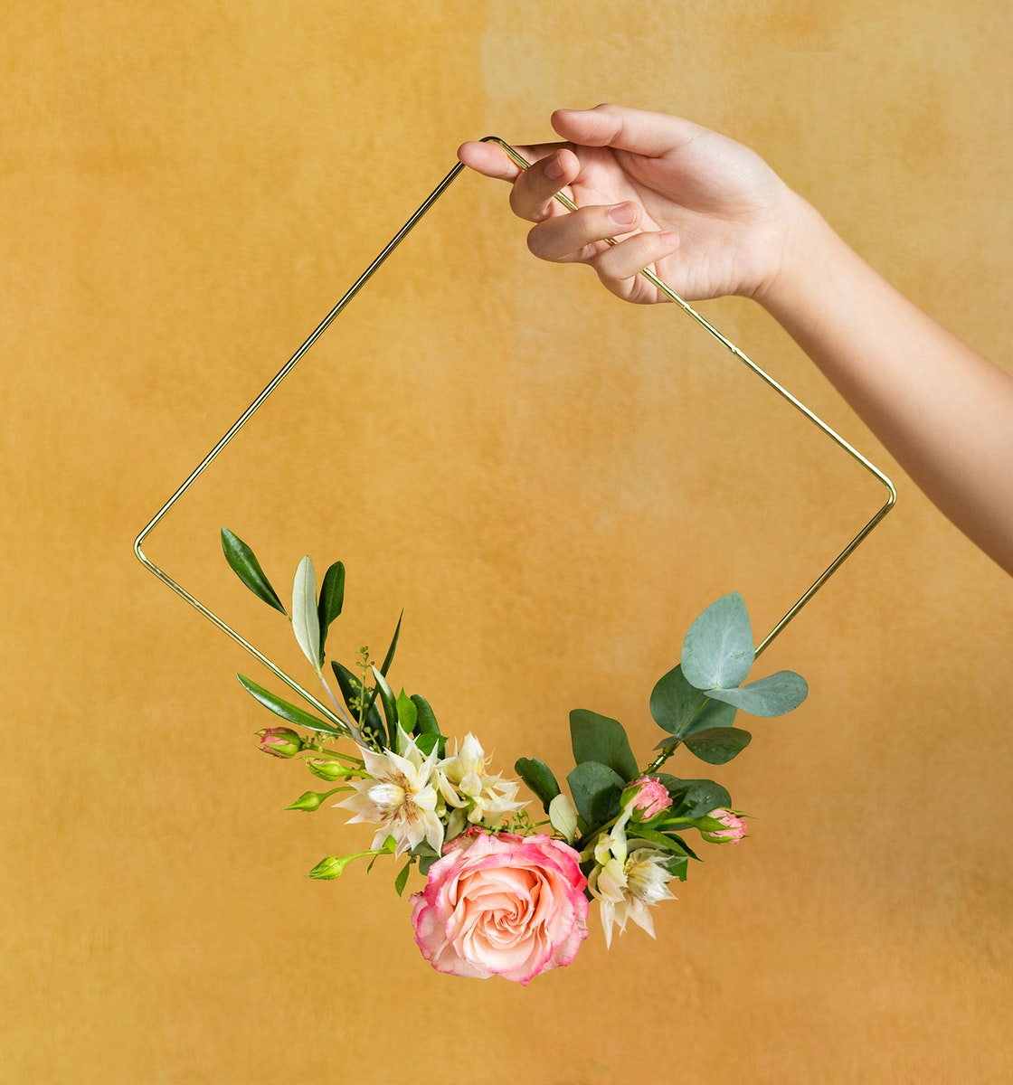 Woman holding a gold frame decorated with flowers