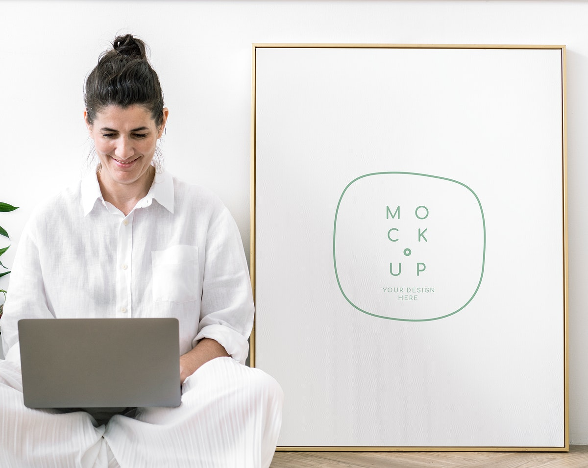 Woman with a laptop sitting by a frame mockup