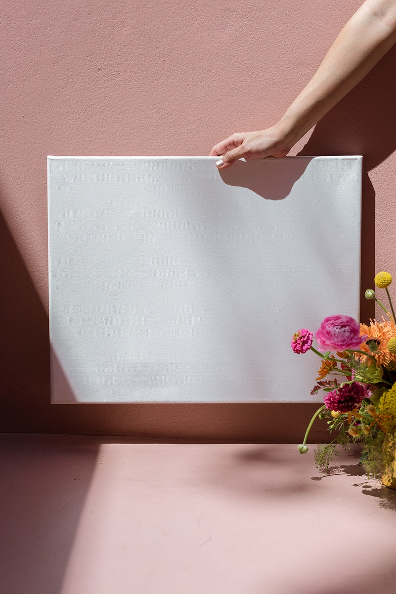 Woman holding a blank frame mockup against a pink wall