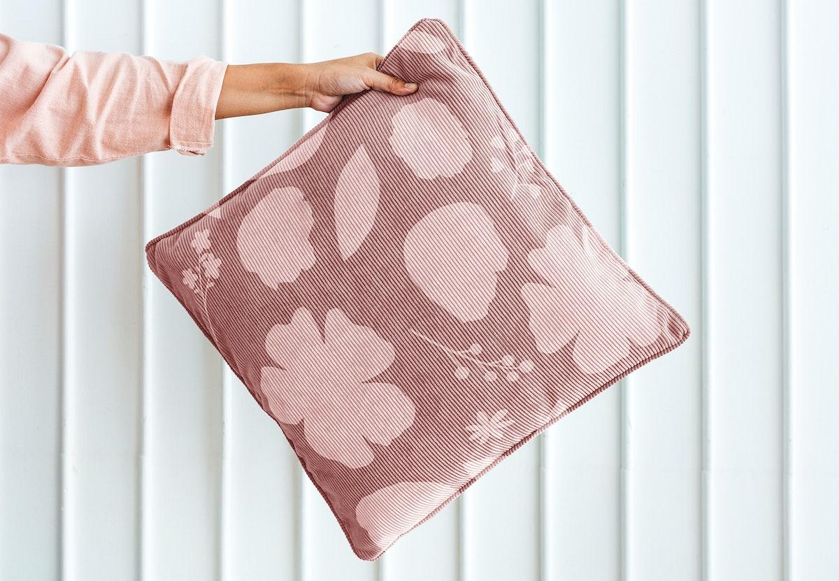 Woman holding pink foliage patterned cushion