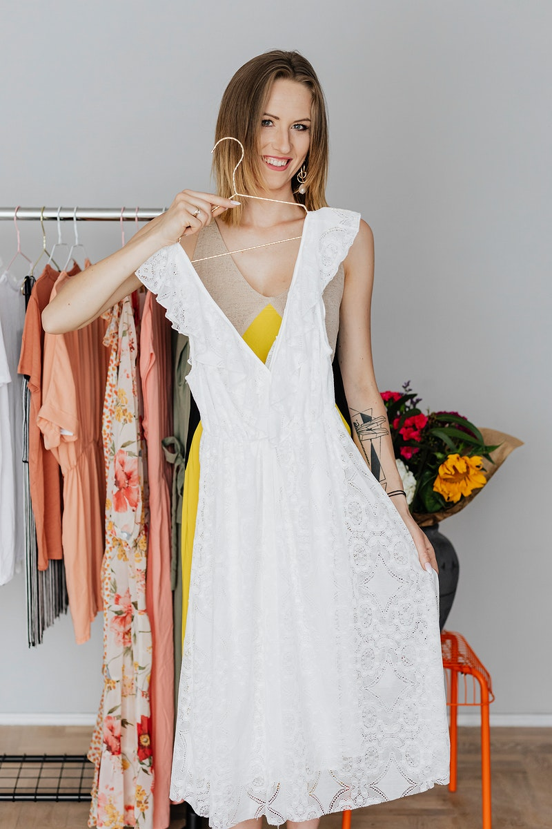 Woman trying a white dress on her