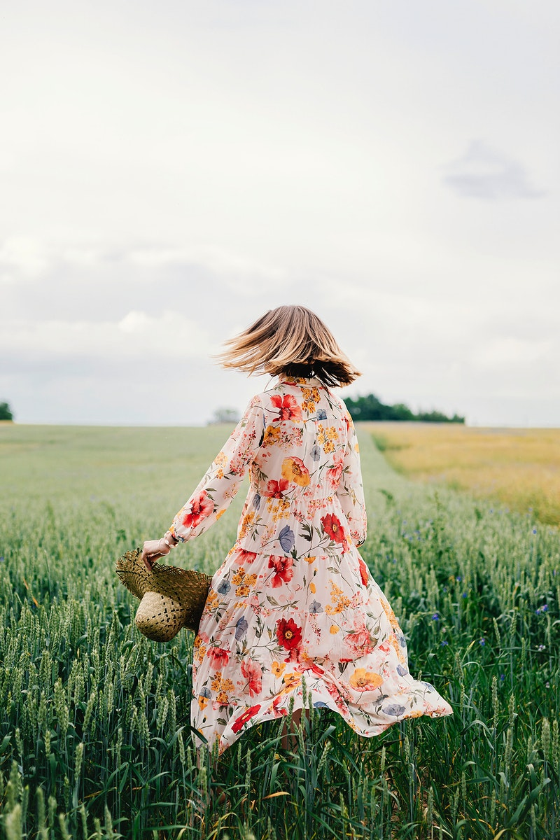 Woman in a floral dress with a woven hat in a field