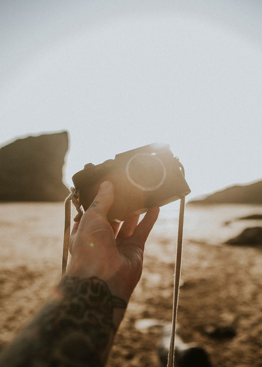 Tattooed man holding a compact camera at the beach