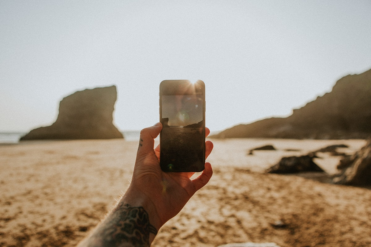 Tattooed man using a mobile phone camera on the beach