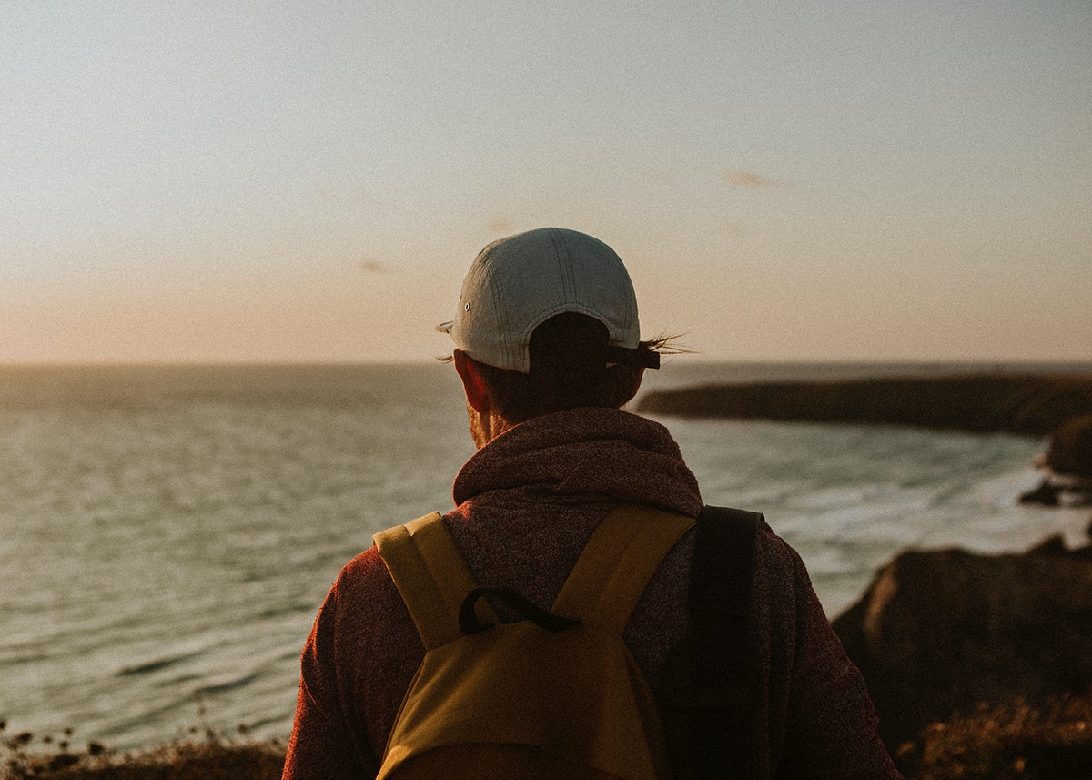 Man watching the sunset from a cliff