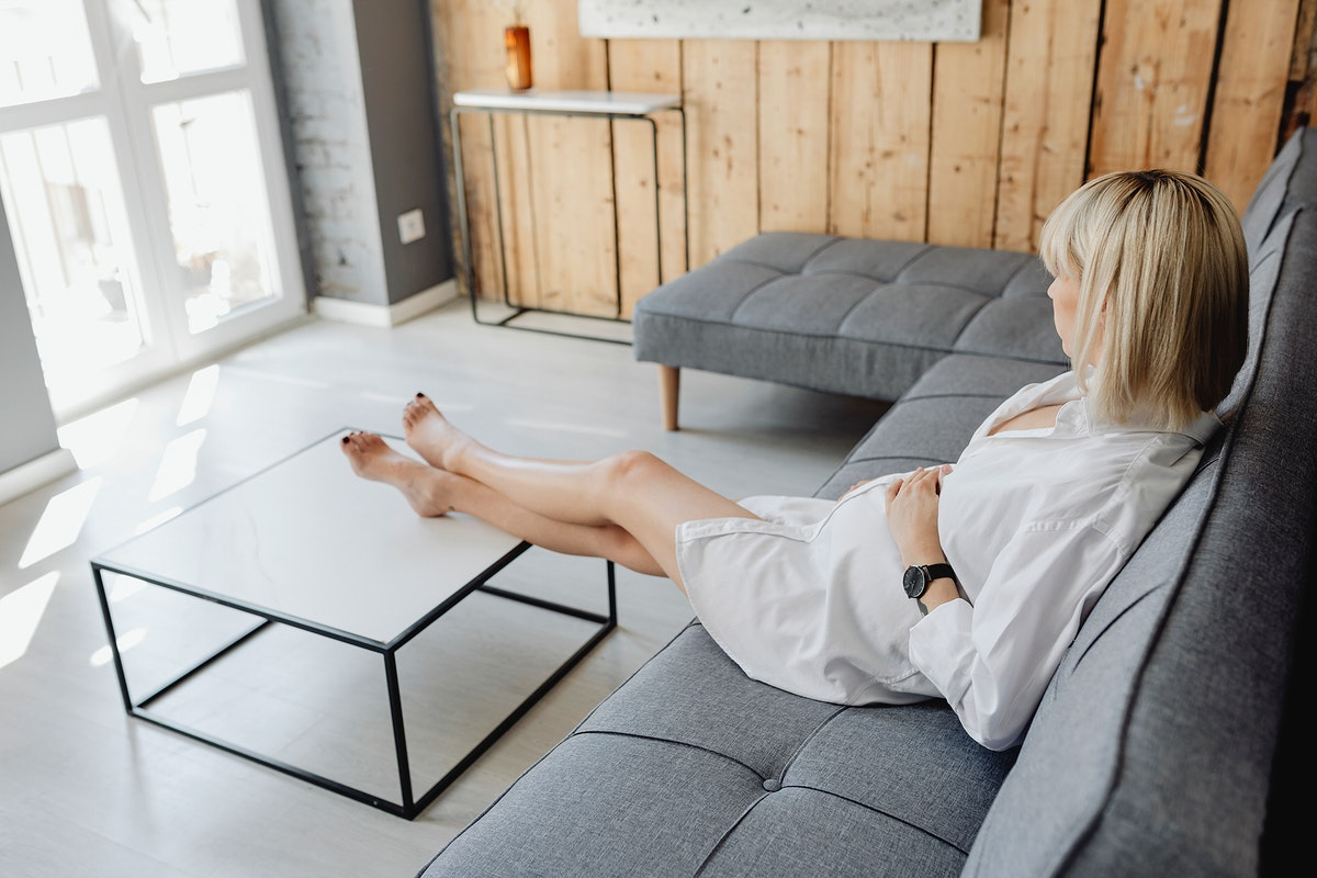 Pregnant blond-haired woman relaxing on a gray sofa
