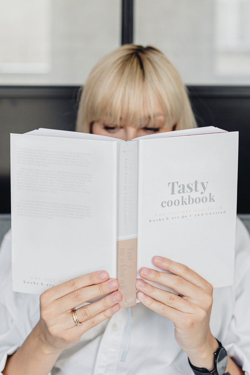 Short blond-haired woman reading a book on a gray couch