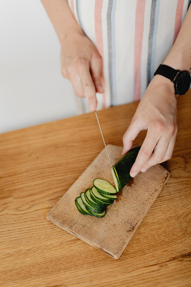 Expecting mother cutting zucchini in the kitchen