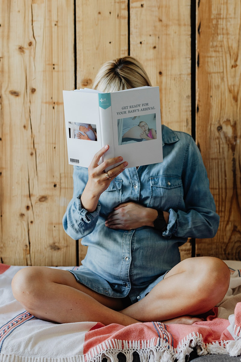 Pregnant woman in a denim dress reading a book on a couch