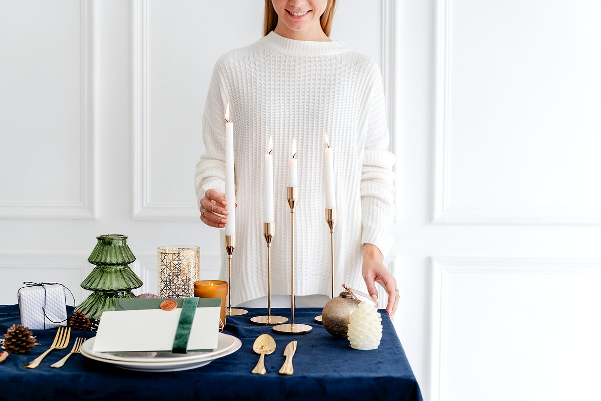 Woman decorating a Christmas dining table with candles