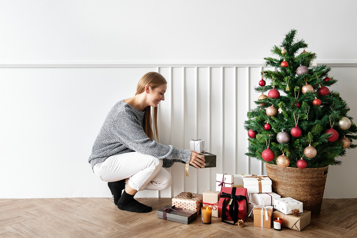 Blond girl decorating a Christmas tree with presents