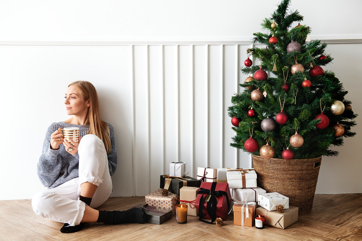 Blond girl sitting next to a Christmas tree