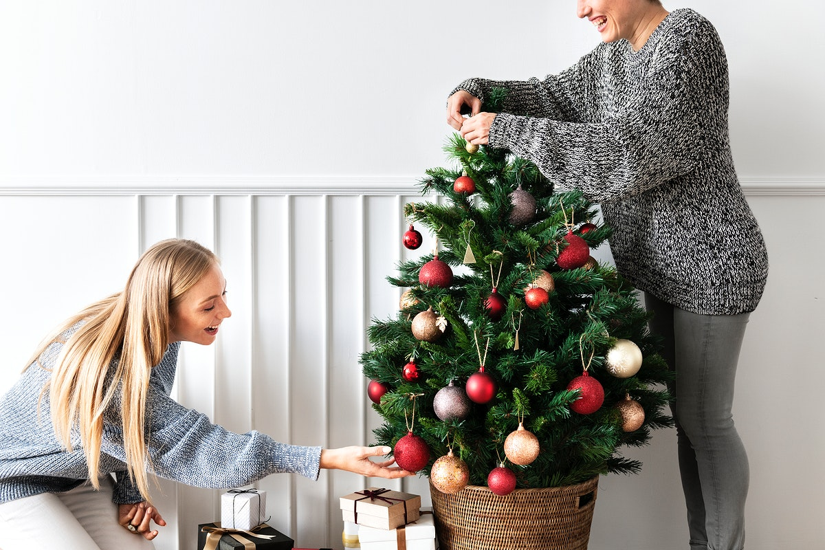 Woman decorating a Christmas tree with ornaments