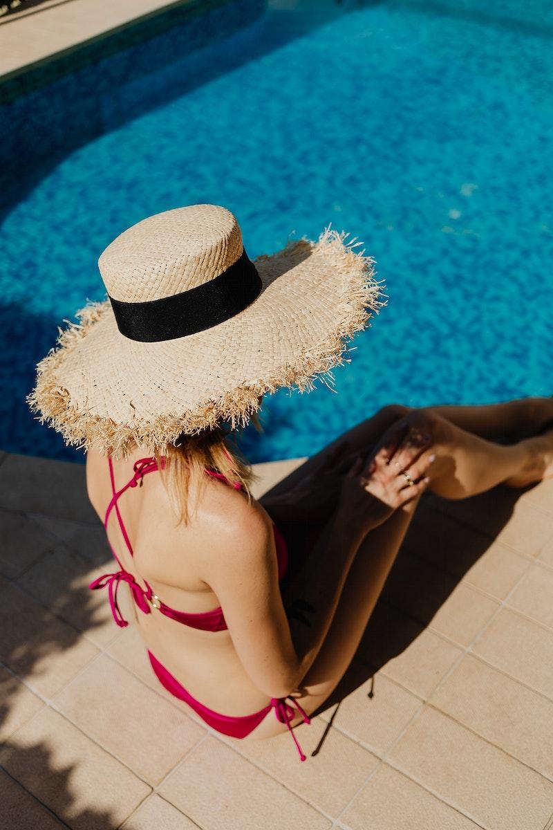 Woman in a pink bikini sitting by the pool