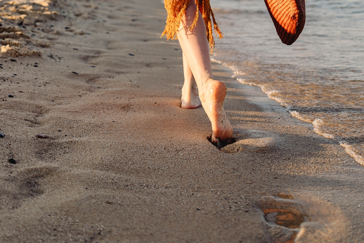 Girl in a brown dress walking alone the beach