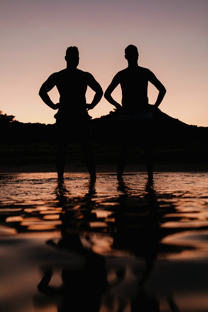 men standing at the beach in the evening silhouette