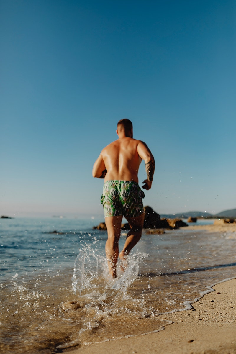 Rearview of man jogging alone the beach