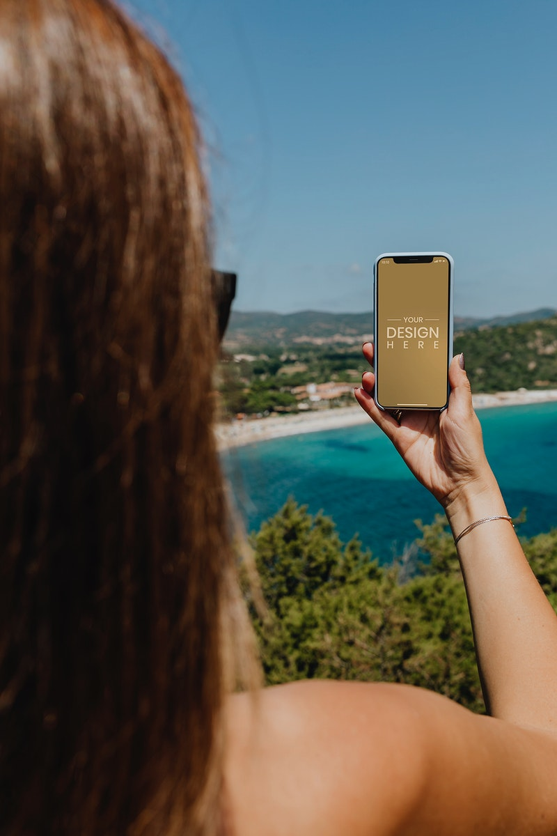 Woman holding a phone at the beach mockup