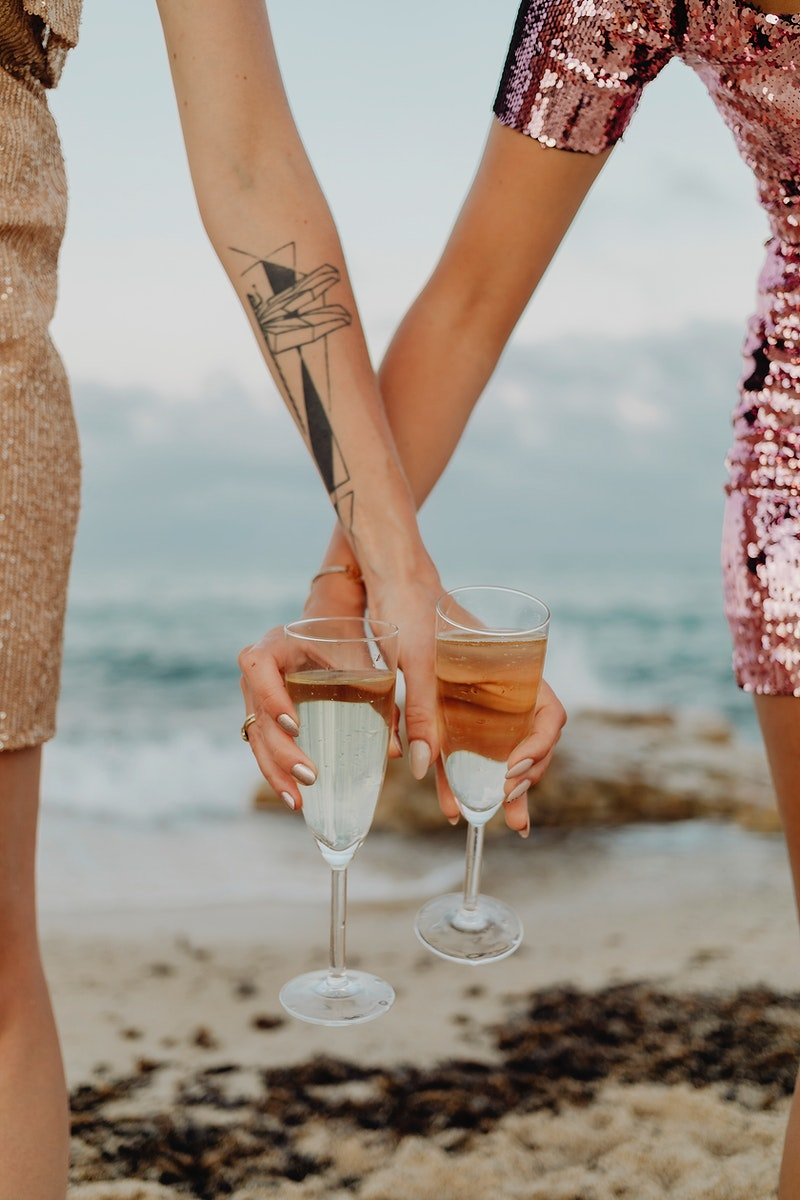 Women with glasses of champagne at the beach