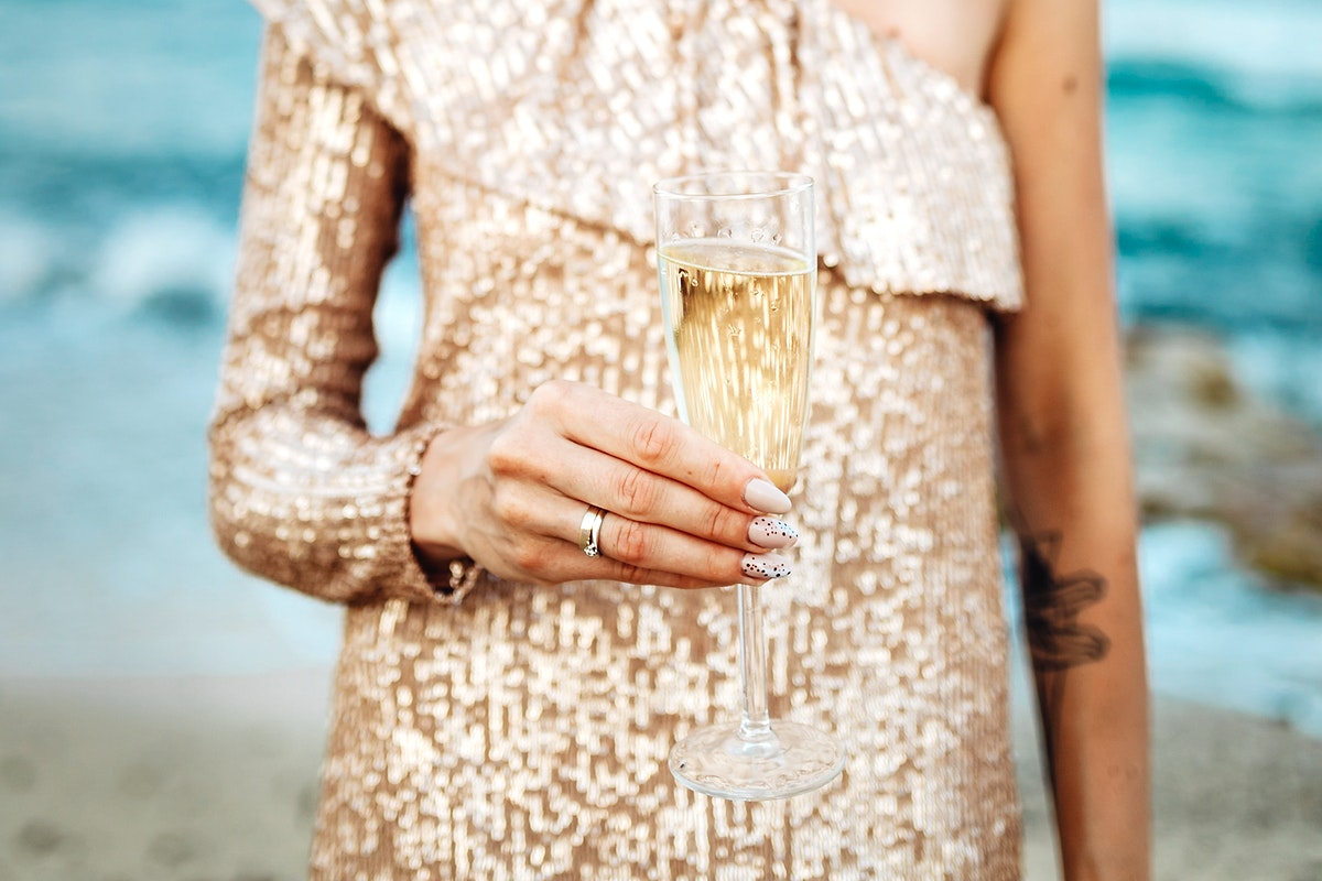 Woman in a gold dress having a glass of champagne at the beach