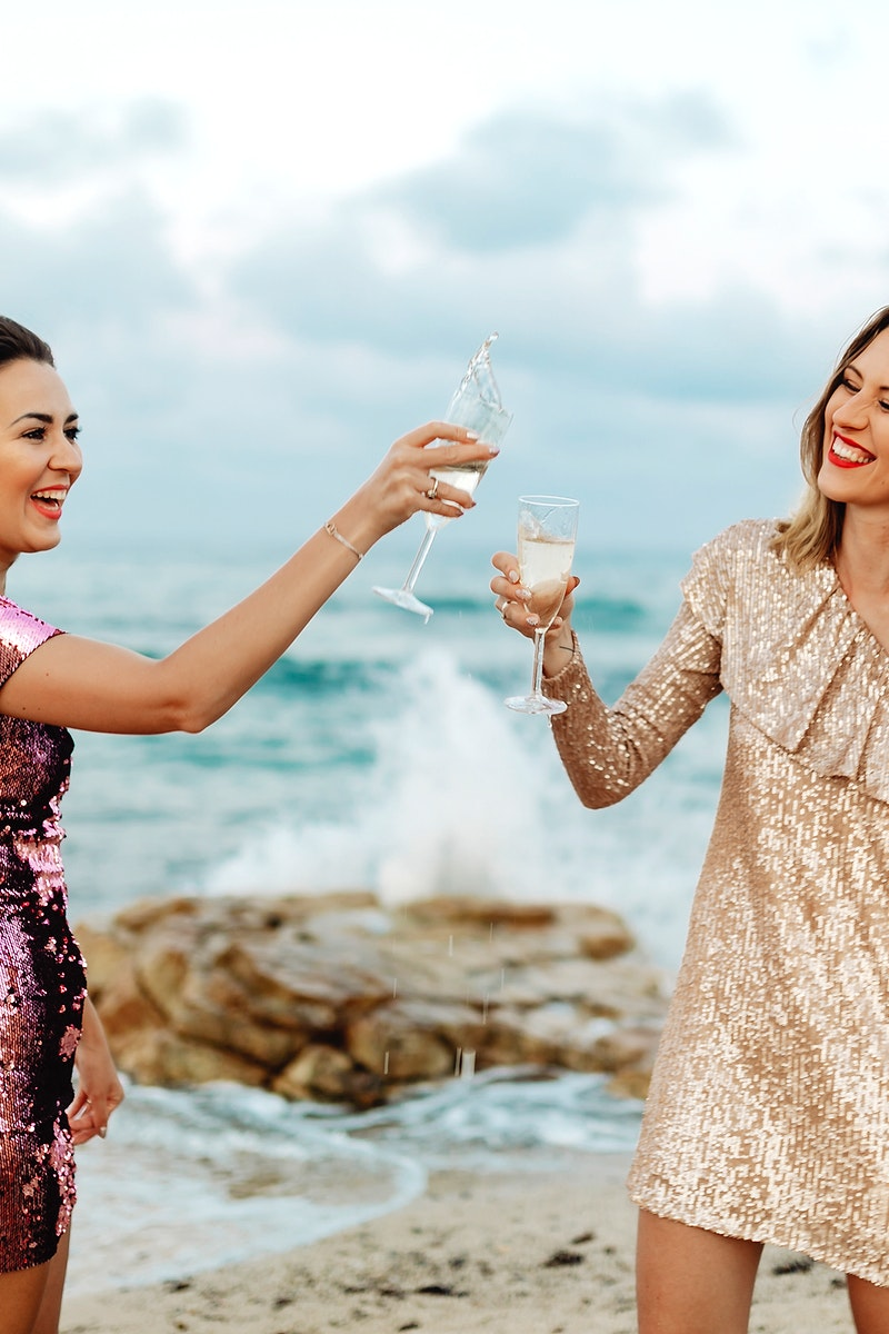 Women clinking  glasses of champagne at the beach