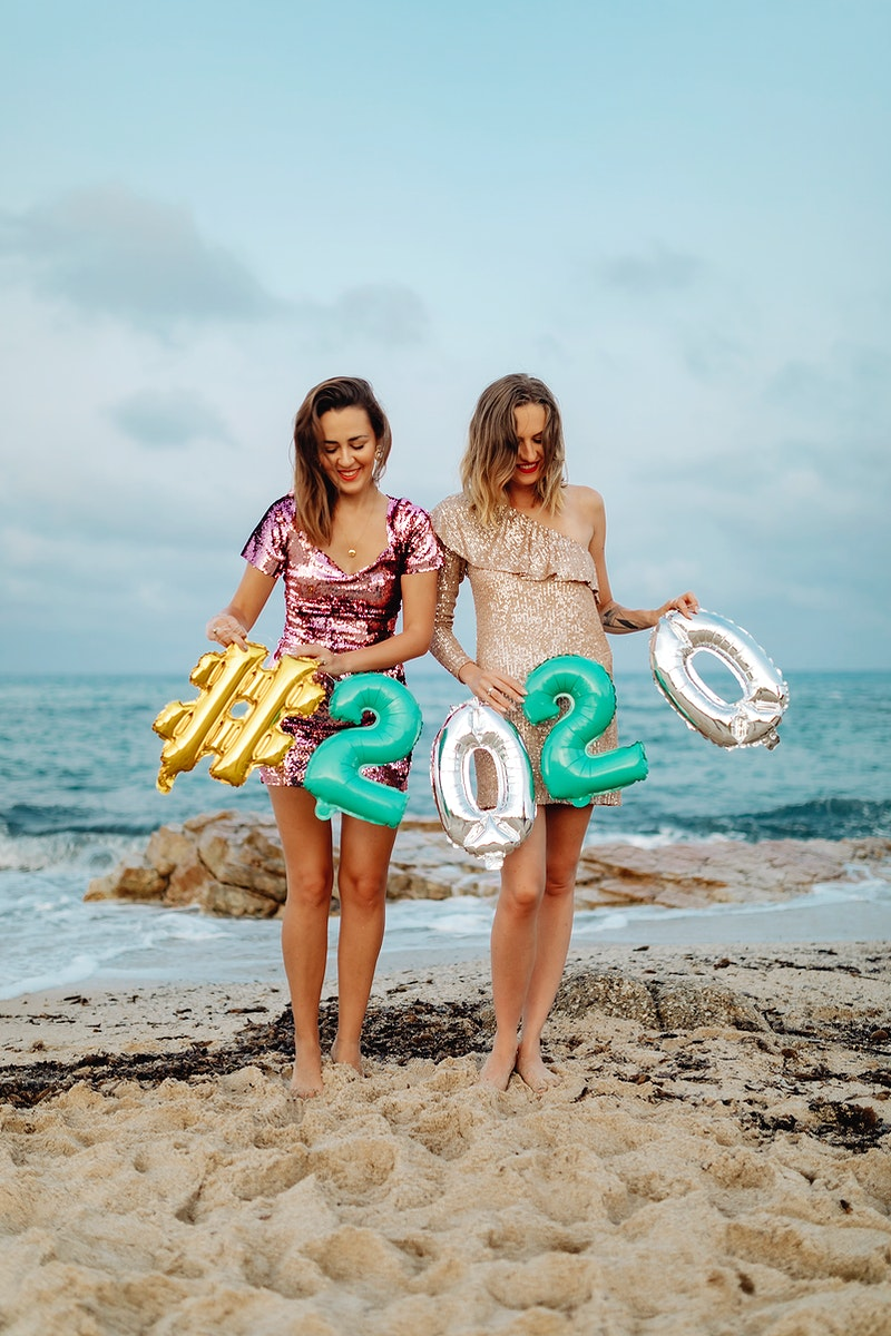 Girls carrying a 2020 foil balloon at the beach party