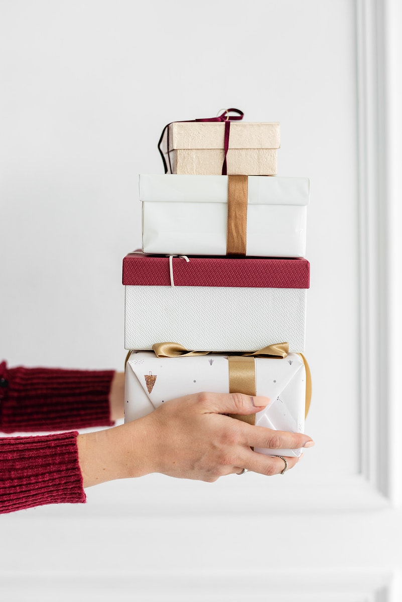 Woman carrying a stack of presents