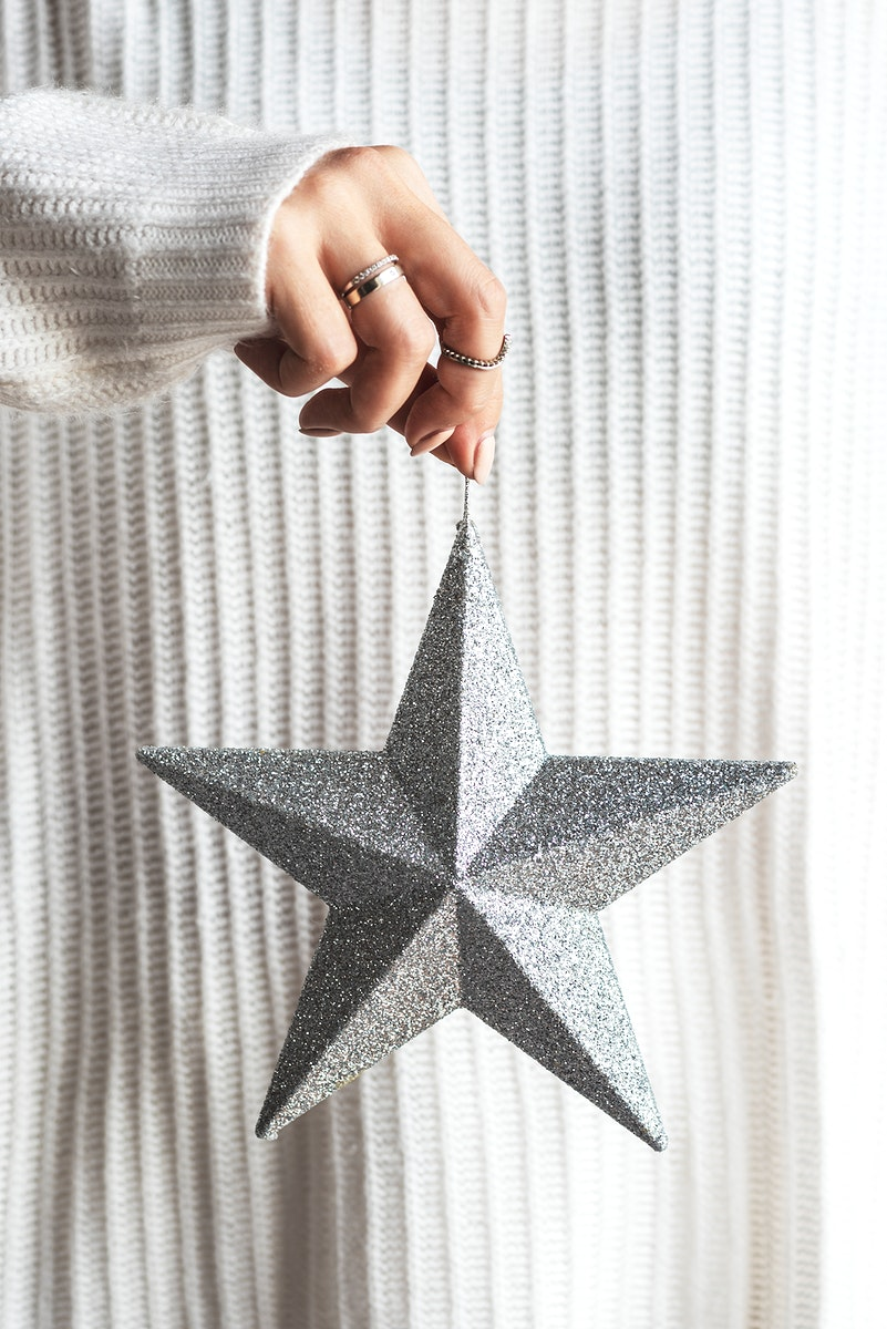 Woman holding a glittery silver star Christmas ornament